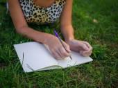 Dziewczyna coś pisze i leżąc na trawie w parku lato — Zdjęcie stockowe