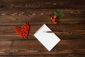 Ashberry as a heart shape at the table and pencil on notebook: wooden background — Foto Stock