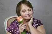 Portrait of happy aged woman with orange rose — Stock Photo