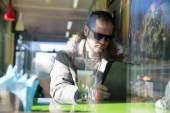 Russian man with beard sitting inside a cafe in glasses — Zdjęcie stockowe