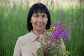 Senior brunette woman with willow-herb in field — Stock Photo