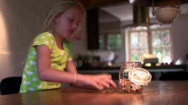 Girl filling coins jar — Stock Video