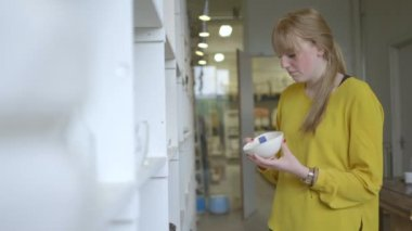 Female potter checking pottery in workshop — Stock Video