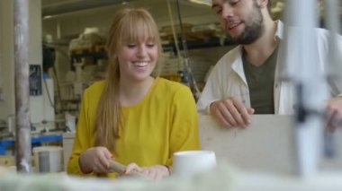 Male potter teaching pottery to woman — Stock Video