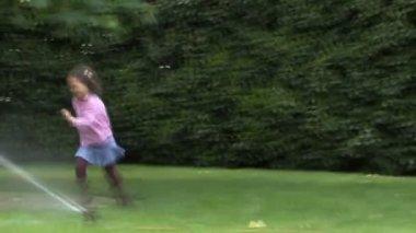 Girl running through sprinkler — Stock Video