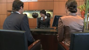 Businesspeople checking in reception desk — Stock Video