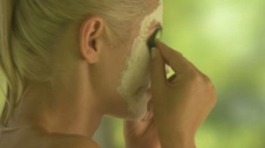 Woman wearing face mask with cucumber — Stock Video