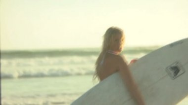 Female surfer carrying surfboard — Stock Video