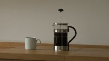 French press and coffee cup on table — Stock Video