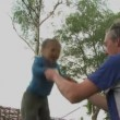 Father helping daughter jump on a trampoline — Stock Video #67026569