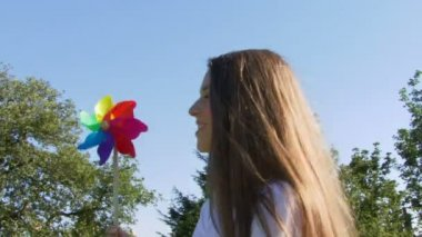Female blowing on a pinwheel — Stock Video