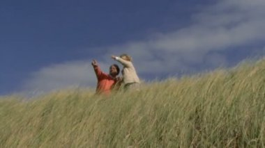 Father and daughter on dunes — Stockvideo