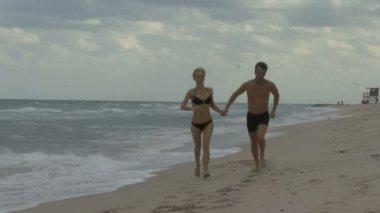 Couple walking along a beach — Stock Video