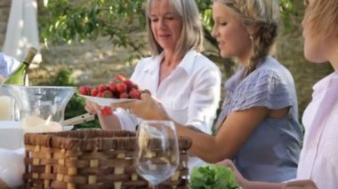 Family passing on strawberries around table — Stock Video