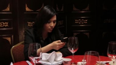 Female in restaurant looking at mobile — Stock Video
