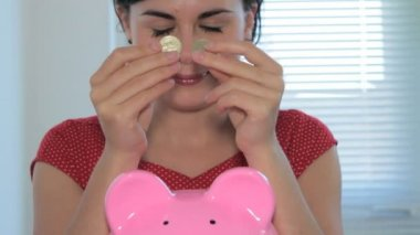 Female putting coins in piggy bank — Stock Video