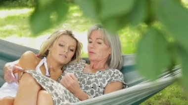 Mother and daughter talking in hammock — Vídeo stock