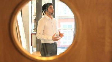 Businesssman talking on headset in office — Stock Video