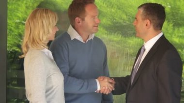 Couple with estate agent in front of house — Stock Video