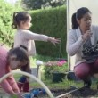 Mother and daughters planting near greenhouse — Stock Video #67046029