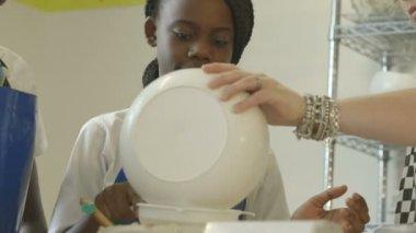 Schoolgirl straining flour — Stock Video