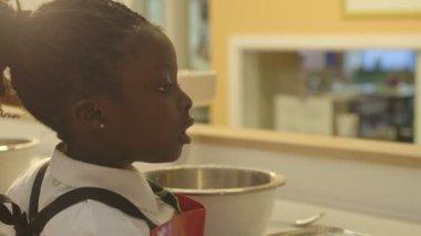 Schoolgirl pouring flour — Stock Video