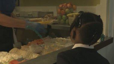 Woman serving schoolgirl — Stock Video