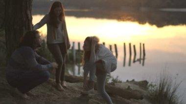 Friends talking on riverbank — Stock Video
