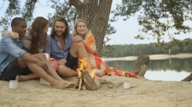 Couples sitting near campfire — Stockvideo