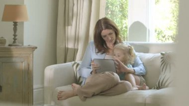 Mother showing digital tablet to her daughter — Stock Video