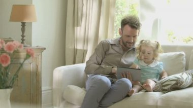 Father showing digital tablet to his daughter — Stock Video