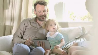 Parents showing digital tablet to her daughter — Stock Video