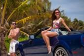 Beach couple near convertible car on the beach. — Stock Photo