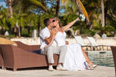 Young wedding couple sitting on the sunbed — Stock Photo