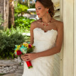 Bride with flowers stays near white wall — Stock Photo #78050546