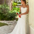 Bride with flowers stays near white wall — Stock Photo #78051502