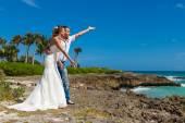Beach couple throws coins into the ocean — Stock Photo