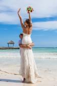 Guy holds girl on hands. Ocean beach — Stock Photo