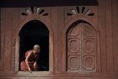 Young monk  on window at Nyan Shwe-Kgua temple , Inle lake in Myanmar. — Stock Photo
