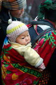 Hmong woman carrying child and wearing traditional attire. — Photo