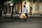 Mulher que carrega a mercadoria na rua em Hanoi, Vietnam. — Fotografia Stock