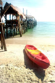 Canoe on the beach and traditional wooden bridge. — Stock Photo