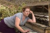 Woman Playing Wooden Piano in Desert with Contemplative Expressi — Stock Photo