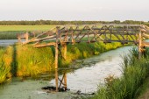 Wood bridge over quiet stream — Stock Photo