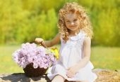 Summer sunny portrait charming curly little girl with floral bas — Stock Photo