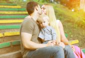 Happy family in  summer day, parents kiss and child — Stock Photo
