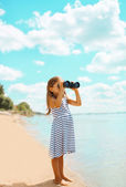 Child looking through binoculars in the expanse of the sea — Stock Photo