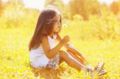Little child blowing dandelion in sunny summer day — Stock Photo