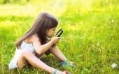 Little girl looking through a magnifying glass on flower — Stok fotoğraf