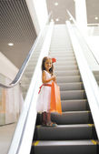 Little girl with shopping bag in mall — Stock Photo